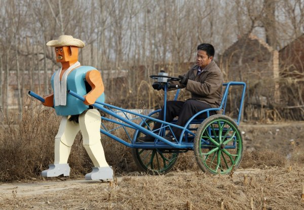 farmer-wu-yulu-drives-his-rickshaw-pulled-by-a-his-self-made-walking-robot-near-his-home-in-a-village-at-the-outskirts-of-beijing-january-8-2009